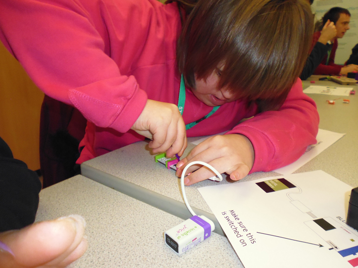 Rachel altering the pulse of LED lights with screwdriver